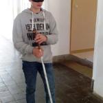 Egy gimnazista fiú bekötött szemmel fehér bottal próbál közlekedni.