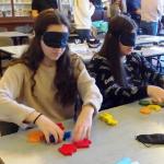 Egy gimnazista lány bekötött szemmel az azonos formájú darabokat keresi.
